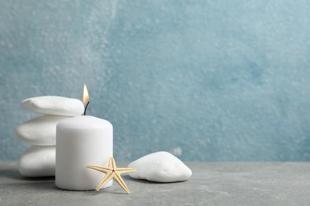 Piedras de mar, velas y seastar sobre fondo gris, espacio de copia. concepto de spa
