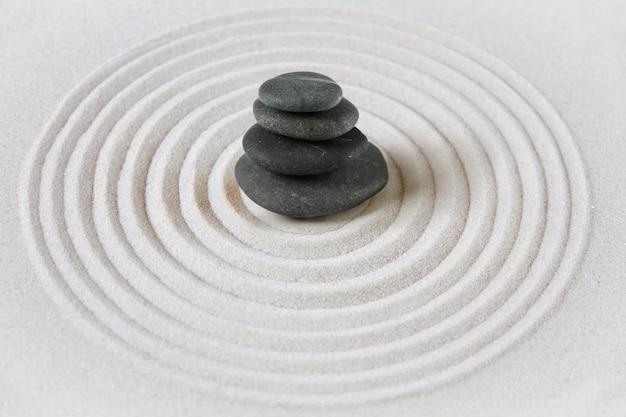 Las piedras negras se amontonan en la arena. escena de fondo del jardín japonés zen