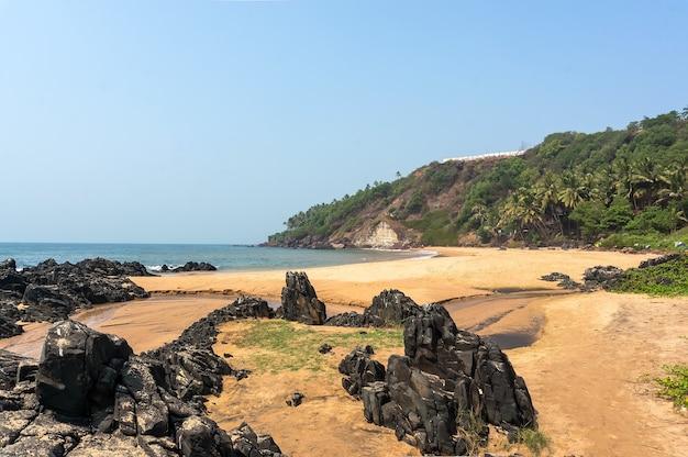 Piedras en las orillas arenosas de la playa. una playa pública, vasco da gama. goa, india
