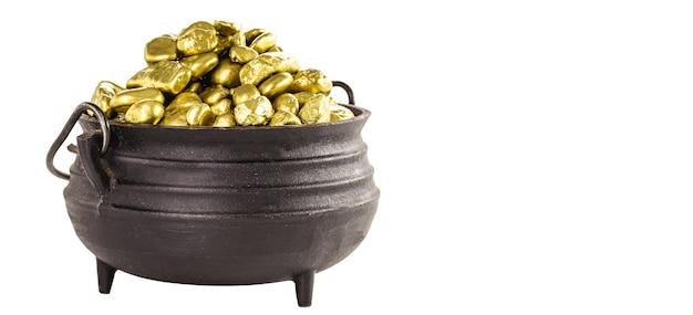 Piedras de oro en olla metálica, concepto de beneficio o gran premio, con espacio de copia y fondo blanco.