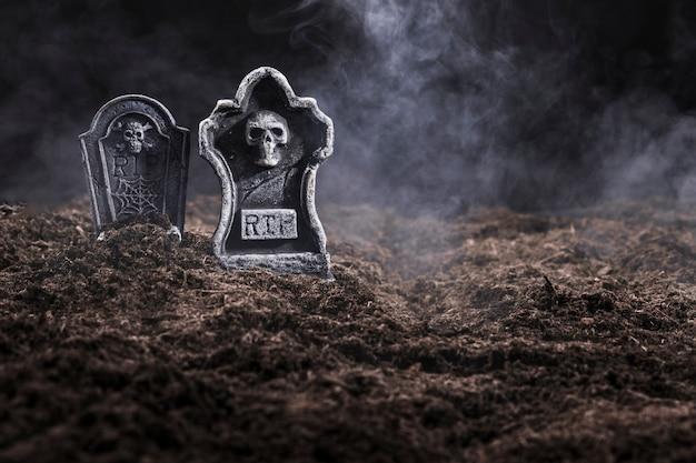 Piedras sepulcrales en el cementerio nocturno en la niebla