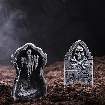 Piedras sepulcrales con cráneo y huesos en el cementerio nocturno