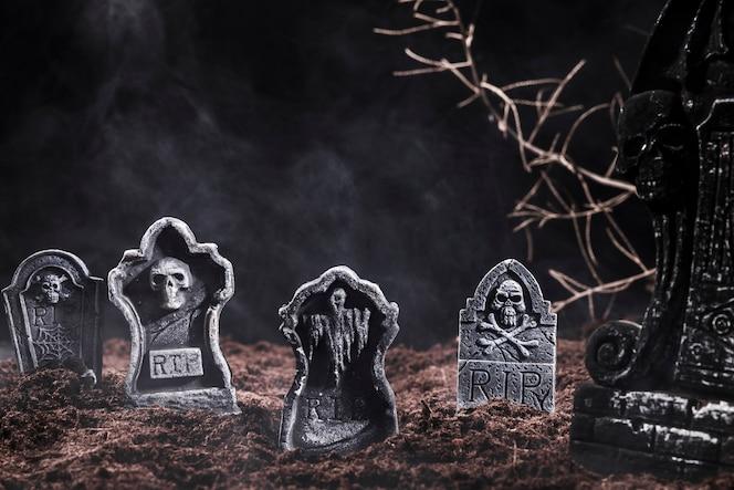 Piedras sepulcrales y ramas en el cementerio nocturno