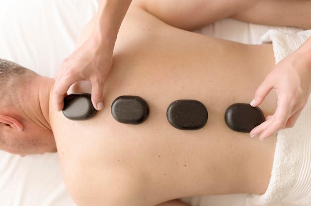 Piedras de spa en la espalda del hombre