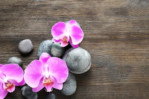 Piedras de spa y orquídeas en madera
