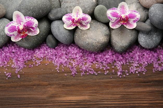 Piedras de spa y orquídeas en mesa de madera