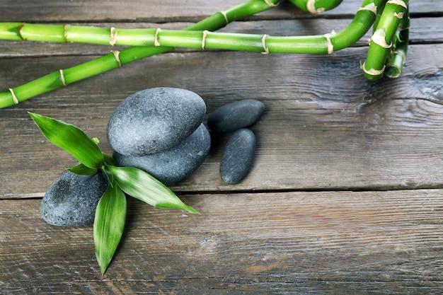 Piedras de spa y rama de bambú en mesa de madera