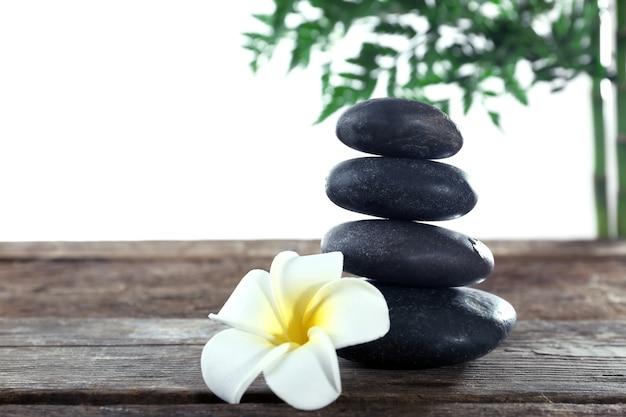 Piedras de spa, una vela y un loto, aislado en blanco