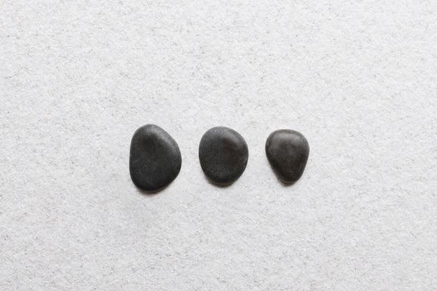Piedras zen negras apiladas sobre fondo blanco en concepto de bienestar