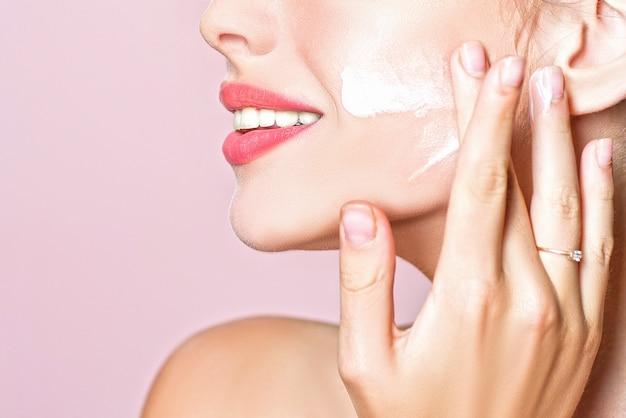 Piel natural. ciérrese encima del retrato de la belleza de una mujer hermosa de risa que aplica la crema de cara. concepto facial limpio y de belleza.