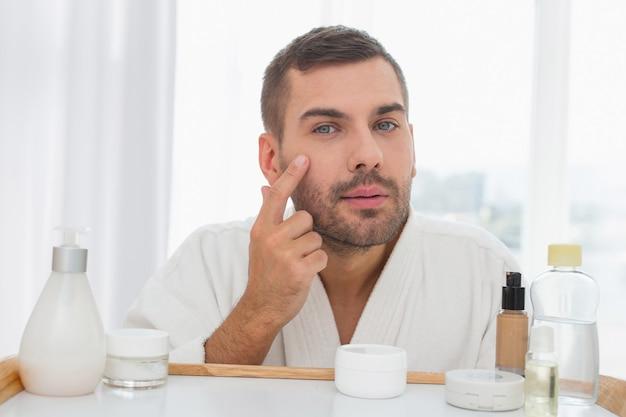 Piel perfecta. hombre joven atractivo que mira su rostro mientras se aplica la crema