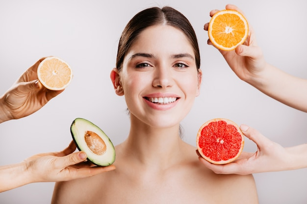 Piel radiante hermosa sana de mujer sin maquillaje. retrato de niña sonriendo contra la pared de frutas.