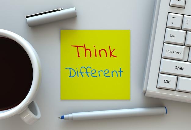 Piensa diferente, mensaje en papel, computadora y café en mesa