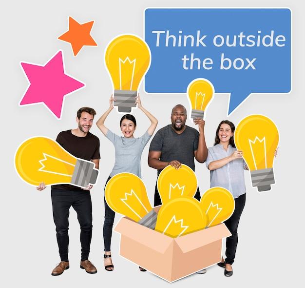 Piensa fuera de la caja personas con símbolos de bombilla.