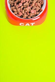 Pienso seco para gatos en un recipiente rojo con espacio de copia