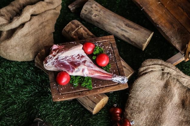 Pierna de cordero cruda en el tablero de madera sal tomate verdes vista superior de maderas
