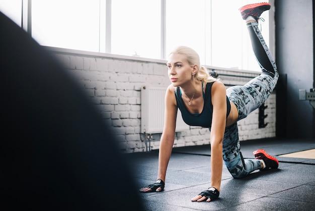 Pierna de elevación de mujer atractiva en el gimnasio