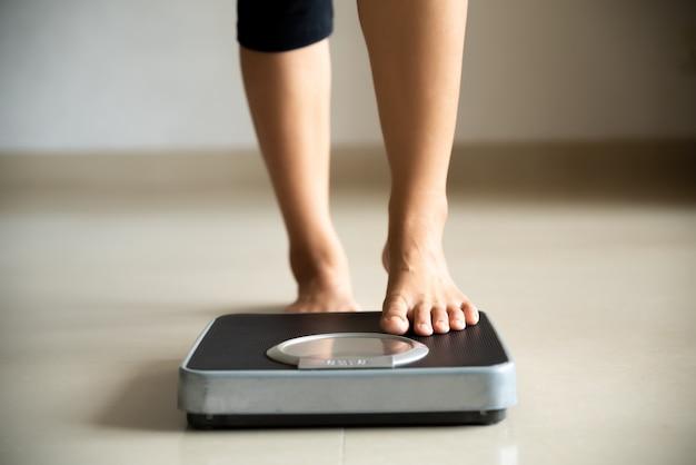 Pierna femenina pisando balanzas. concepto de estilo de vida saludable, comida y deporte.