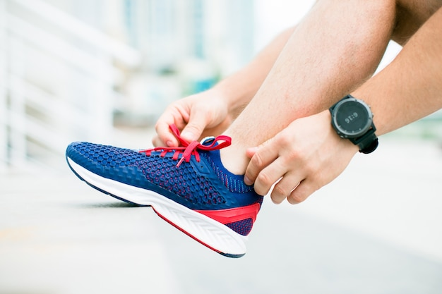 La pierna del hombre en calzado deportivo descansa sobre un banco. mano con relojes deportivos.