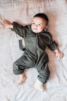 Pierna izquierda del niño asiático bebé pequeño en férula, acostado en la cama.