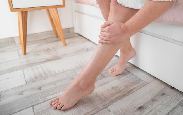 Pierna de masaje de mano de primer plano