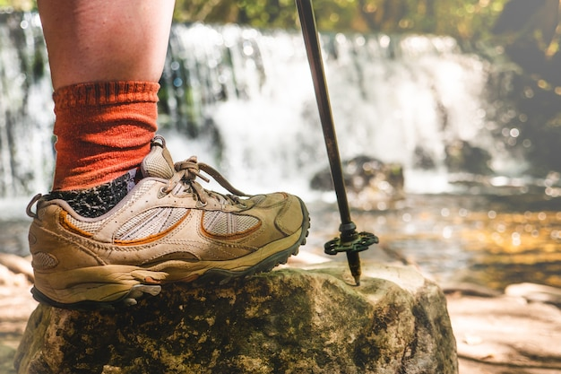 Pierna de mujer con botas de montaña y palo sobre una roca con una cascada natural detrás