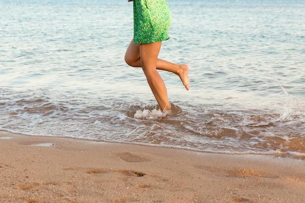 Pierna de mujer corriendo en la playa con salpicaduras de agua