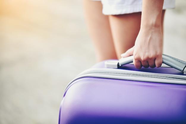 Pierna de mujer con equipaje morado y preparado para irse.