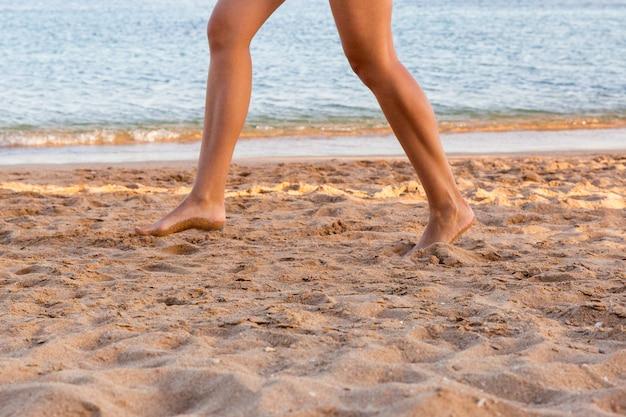 Pierna de la mujer que se ejecuta en la playa de arena. vacaciones de verano.