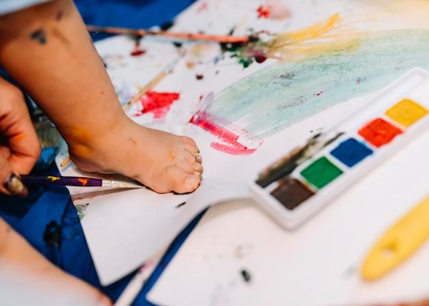 Pierna del niño en el papel cerca de colores de agua