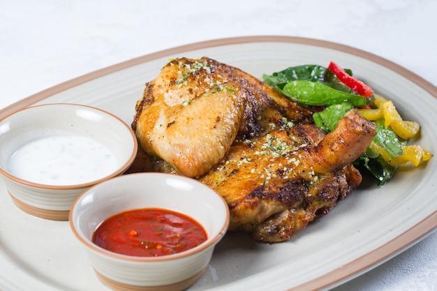 Pierna de pollo en cuartos asados con piel dorada crujiente.