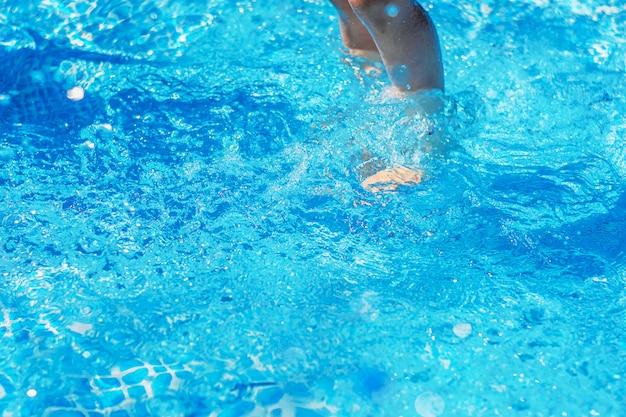 Piernas bajo el agua en primer plano de la piscina azul