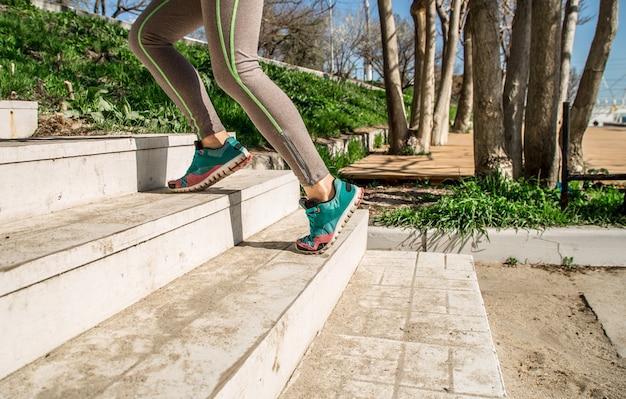 Las piernas atléticas femeninas suben las escaleras
