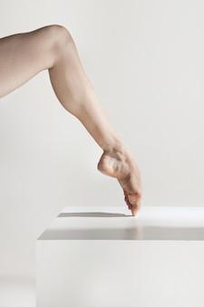 Piernas de bailarina de primer plano en el piso blanco