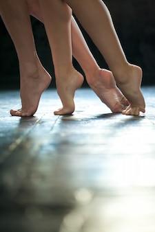 Piernas de bailarina de primer plano en el piso de madera