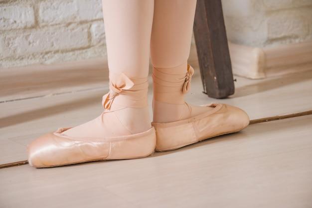 Las piernas de la bailarina primera posición en pointe, fondo del concepto del bailarín de ballet.