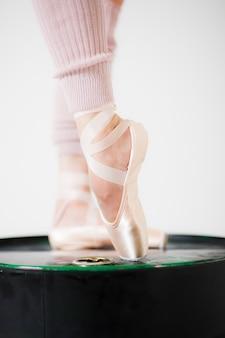 Piernas de bailarina en zapatillas de punta de cerca sobre un fondo blanco.