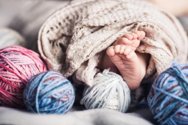 Las piernas del bebé asoman por debajo de las mantas entre enredos de hilo. hermoso concepto de infancia.
