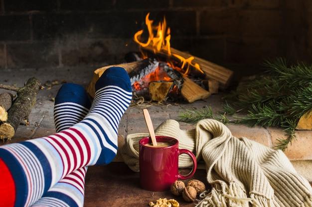 Piernas en calcetines cerca de la chimenea