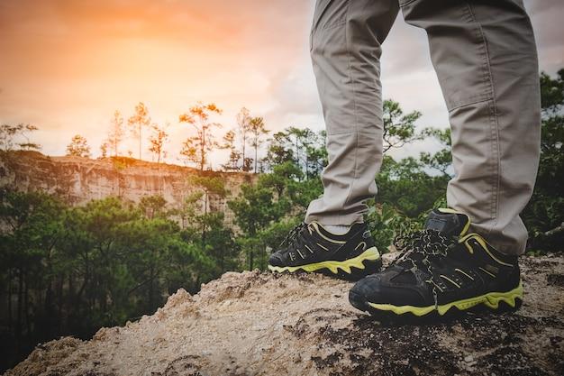 Piernas del caminante del hombre en el pico de la montaña del amanecer