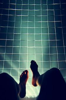 Piernas colgando de la piscina de luz brillante