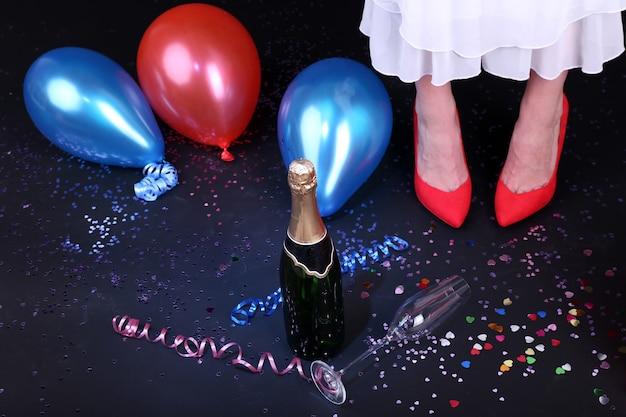 Piernas con confeti, champán y globos en el suelo.