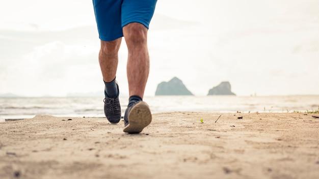Piernas del corredor del hombre que ejecutan el primer en el zapato, hombres que activan en la playa
