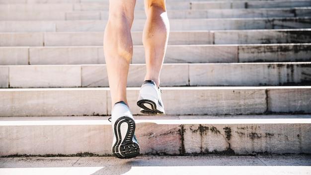 Piernas de cultivo en zapatillas corriendo arriba
