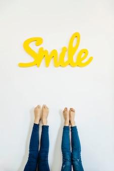 Piernas de cultivos y colorida palabra sonrisa