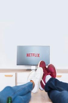 Piernas de cultivos de personas viendo series de televisión