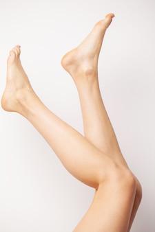 Piernas delgadas femeninas de belleza después de la terapia de spa sobre fondo blanco.