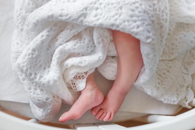 Piernas delgadas del recién nacido en una manta colcha circular alrededor de los pies del bebé un niño cubierto con una manta de punto de encaje