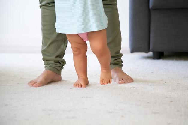 Piernas descalzas del bebé tratando de caminar delante de mamá. niño dando sus primeros pasos con el apoyo de las mamás. toma recortada. concepto de paternidad e infancia