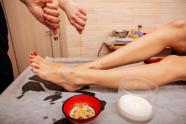 Piernas desnudas. maestro experto profesional remojo el aceite de los tejidos en las piernas afeitadas mientras ella está acostada sobre la mesa de madera